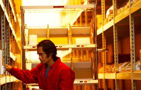 man picking orders using powered, light-directed order picking cart