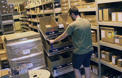 man in warehouse picking orders into boxes on software-driven smart pick cart