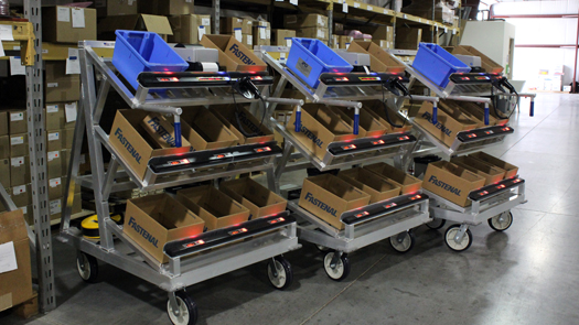 three light-directed picking carts with boxes and totes